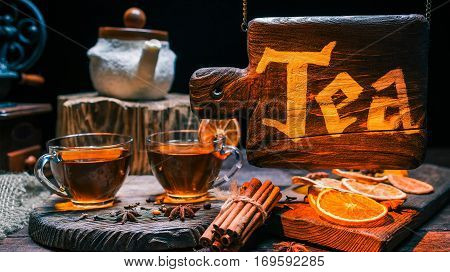 Teacups and spices on wood counter of tea shop with wood hanging sign