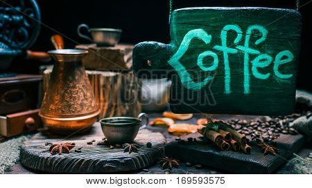 Green and blue lighted wood sign above coffee shop counter with metal cups of coffee, beans and spices