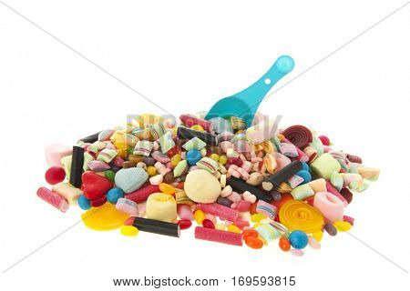 Mixed colorful candy with blue spoon isolated over white background