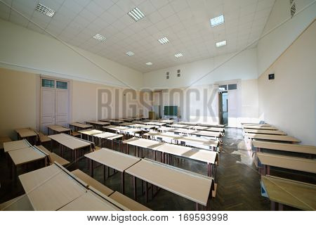 Sunny classroom with rows of tables for students and big window