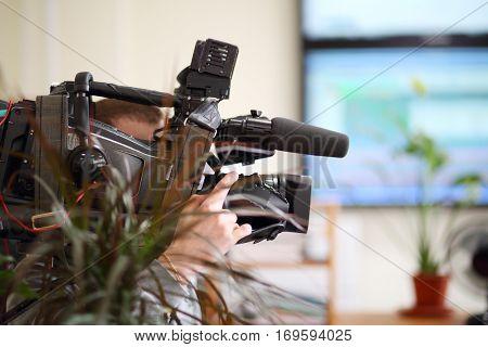 Operator with black camera is recording video in office, shallow dof