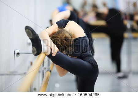 Girl in black leotard stretch at ballet class, other girls out of focus