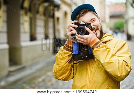 Young hipster with a beard holding oldshool film camera, looking in the camera viewfinder, laughing and ready to take a photo, on the street, wearing in bright raincoat and hat, portrait, day outdoors, closeup