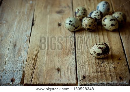 Scattered quail eggs on aged planked wood background, rustic vintage style, minimalist, kinfolk, Easter, tranquility and simplicity concept