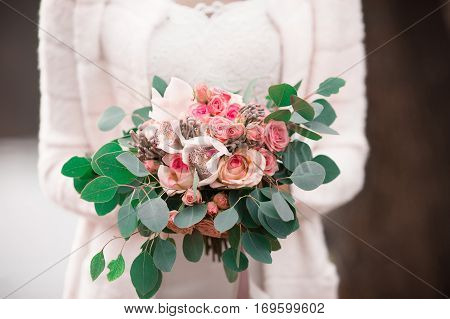 Wonderful pretty bride with wedding bouquet. Wedding flowers. Shallow depth of field. Wedding bouquet close-up. Wedding bouquet of roses in hands of the bride