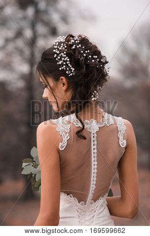 Beautiful bride. Wedding hairstyle and make up. Wonderful pretty bride with wedding bouquet.Closeup portrait of young pretty bride from her back.Beautiful bride with fashion wedding hairstyle.Wedding.