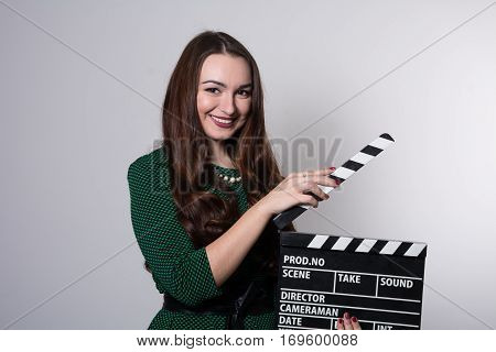 Beautiful Young Girl In Green Dress Is Holding A Clapperboard