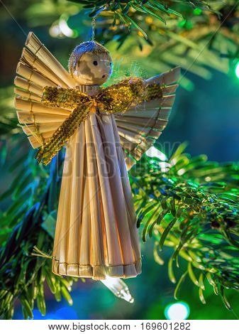 Straw Christmas angel hanging on christmas tree