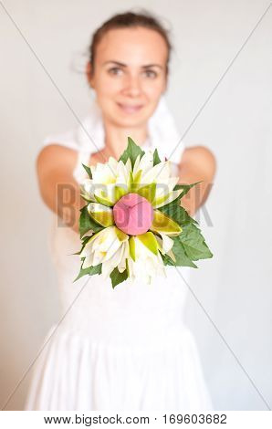 Beautiful young bride shows her wedding bouquet