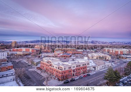 FORT COLLINS, CO, USA - DECEMBER 13, 2016: Downtown of Fort Collins, Colorado at cold winter dawn - aerial view with holiday lights and Rocky Mountains in background..