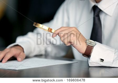 Businessman reading documents with magnifier