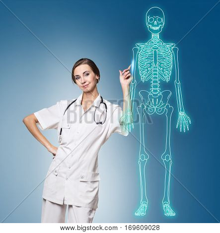 Medical doctor woman pointing on drawing human skeleton, over blue background.