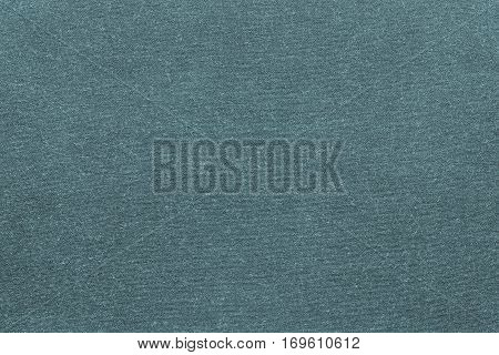 background and texture of knitted or woolen fabric of monotonous turquoise color