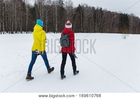 Sporting girlfriend go in winter woods at afternoon