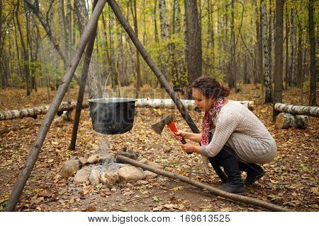 Woman chops wood near bonfire with hanging pot in yellow autumn forest