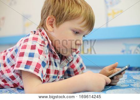 Little hgandsome boy lies on bed and plays with touch phone in room