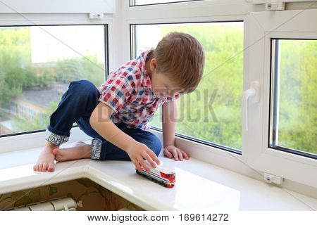 Little happy boy sits on windowsill and plays toy train at summer day