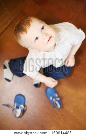 Handsome little boy sits on floor with shoes and looks up in room