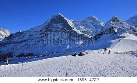Ski and snow covered mountains Eiger Monch and Lauberhorn. Winter day in Grindelwald Swiss Alps.