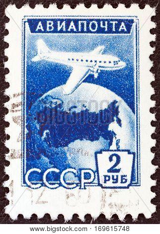 USSR - CIRCA 1955: A stamp printed in USSR shows Ilyushin Il-12 over Globe, circa 1955.