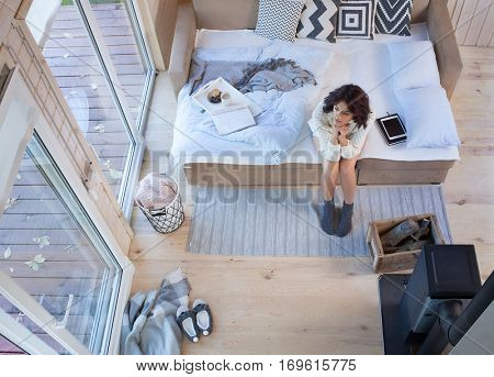 Young beautiful brunette woman sitting down on the bed by the fireplace and window in a wooden cabin. Top view from above.
