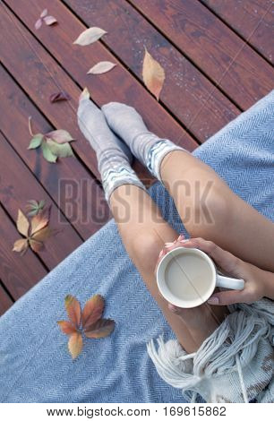 Woman with cup of coffee sitting relaxing on patio wooden deck, she's covered in a blanket. Fall leaves on wooden patio deck. Autumn concept.