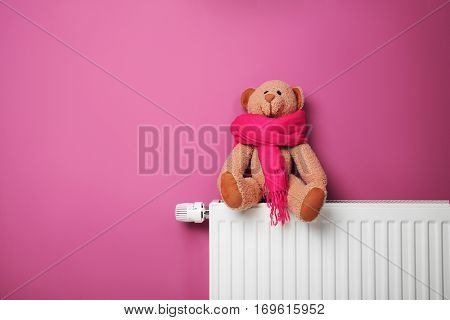 Teddy bear on heating radiator near pink wall