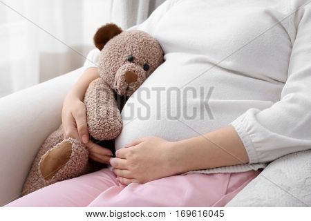 Closeup of pregnant woman with teddy bear sitting on armchair