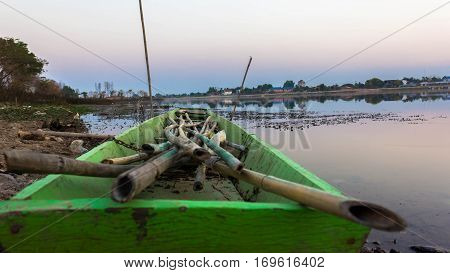 Green boat moored at the shore. In many bamboo tanker The device is used to catch fish