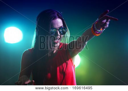 Portrait of pretty young DJ with headphones in nightclub