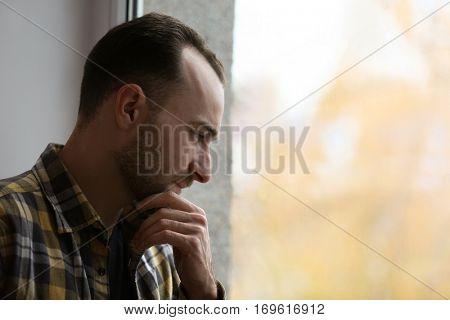 Handsome depressed man near window