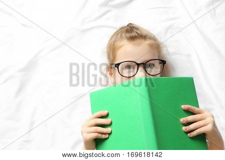 Funny little girl lying on bed with book