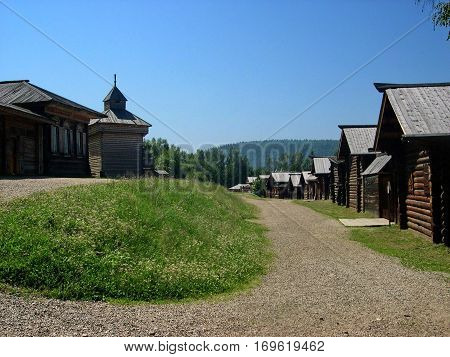 Village Street in the summer. Wooden log huts in the Siberian village. Lake Baikal, Russia