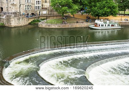 Bath Somerset United Kingdom - June 19 2006: People relaxing in the park near the Pulteney Bridge. The river Avon with weir and tour boat in Bath.
