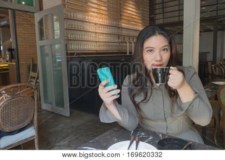 woman shopping online sipping drinking hot coffee and use mobile phone at coffee time at coffee shop or home in garden view and relax atmosphere / woman and coffee