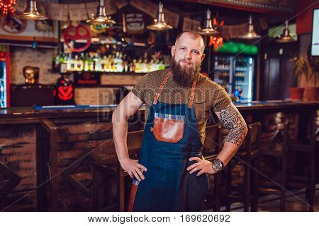 Bearded barman with tattoos and watches wearing an apron standing near the bar.