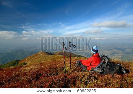 Tourist looking at landscape. Halt in mountains. Woman has bright red outdoorsy clothing. Sky and mountain ranges in background. Red bilberry leaves in foreground. Sticks and backpack near woman.