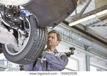 Mid adult technician repairing car's wheel in workshop