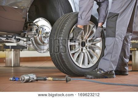 Low section of male mechanic repairing car's tire in repair shop