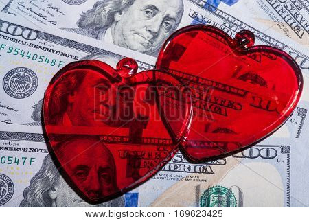 Red glass hearts on dollar bills - close up, concept