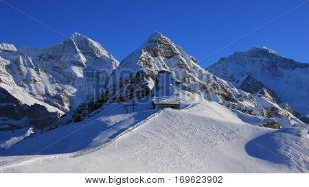 Snow covered mountains Monch Lauberhorn and Jungfrau. Chair lift and ski slope. Winter landscape in Grindelwald Swiss Alps.