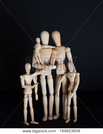Photos wooden dolls, happy family with children on a black background