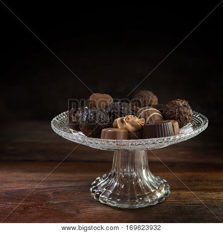 chocolate pralines on a glass étagère on rustic brown wood dark background fades to black generous copy space selected focus narrow depth of field
