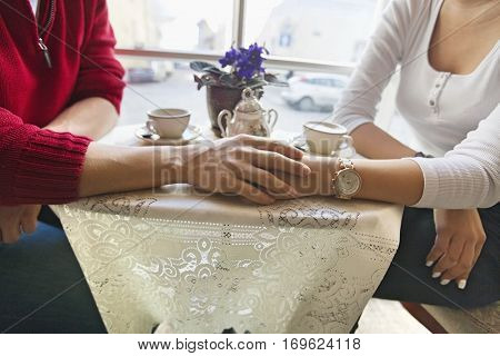 Midsection of couple holding hands in cafe