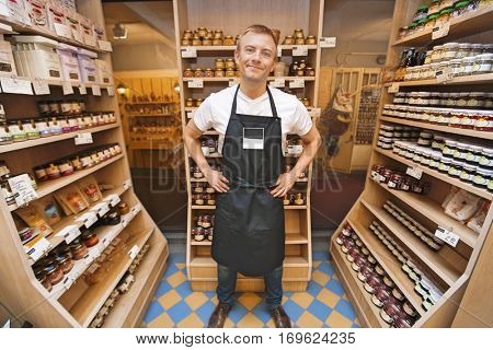 Full length portrait of mid adult salesman standing hands on hips in grocery store