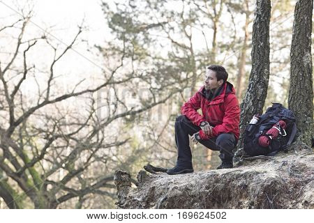 Full length of male hiker crouching on cliff in forest