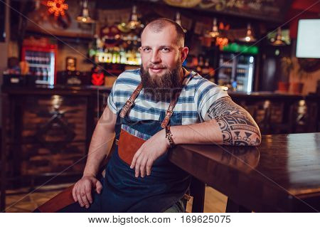 Bearded barman with tattoos and wathes wearing an apron sitting in bar.
