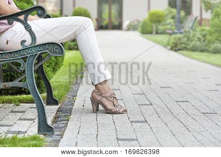Low section of young woman sitting on park bench