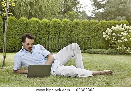 Full length of young man using laptop while reclining in park