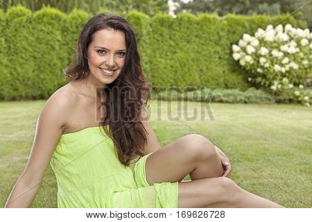 Portrait of beautiful young woman in sundress relaxing in park